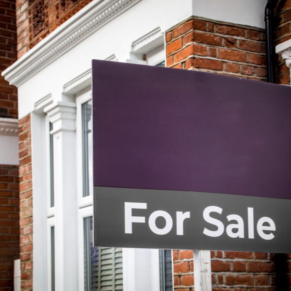 Purple for sale sign outside a home